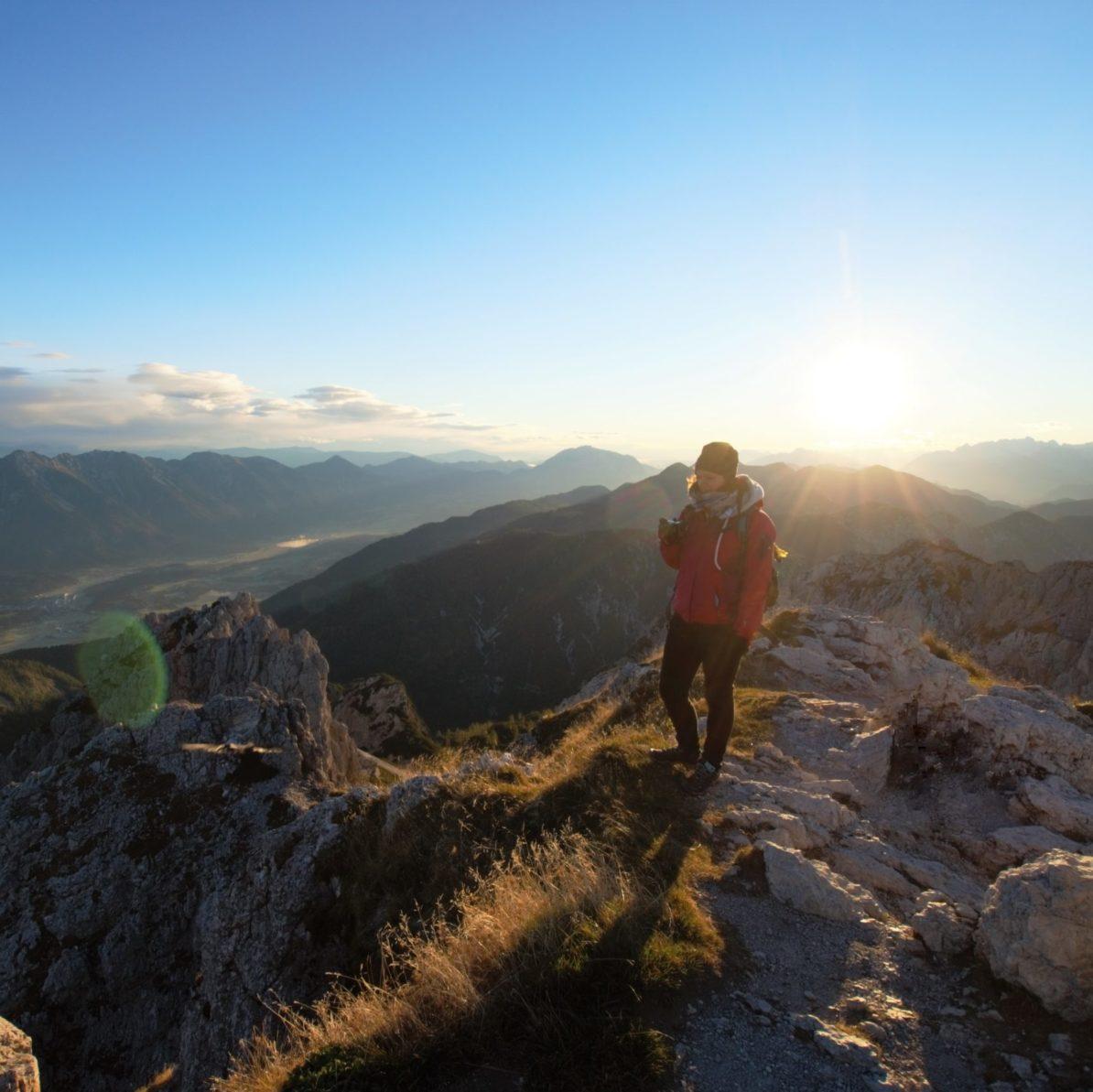 Julia steht bei Sonnenaufgang auf dem Gipfel eines Berges.