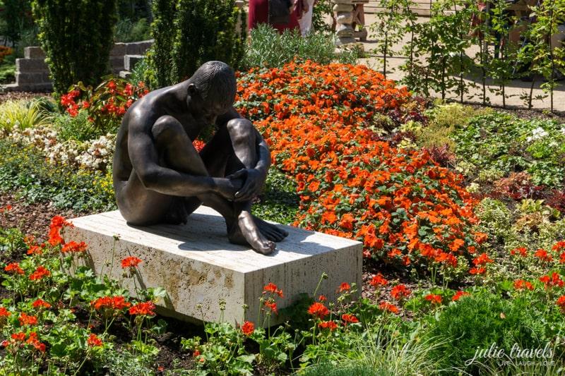 Statue eines Menschen, der auf einem Stein sitzt.