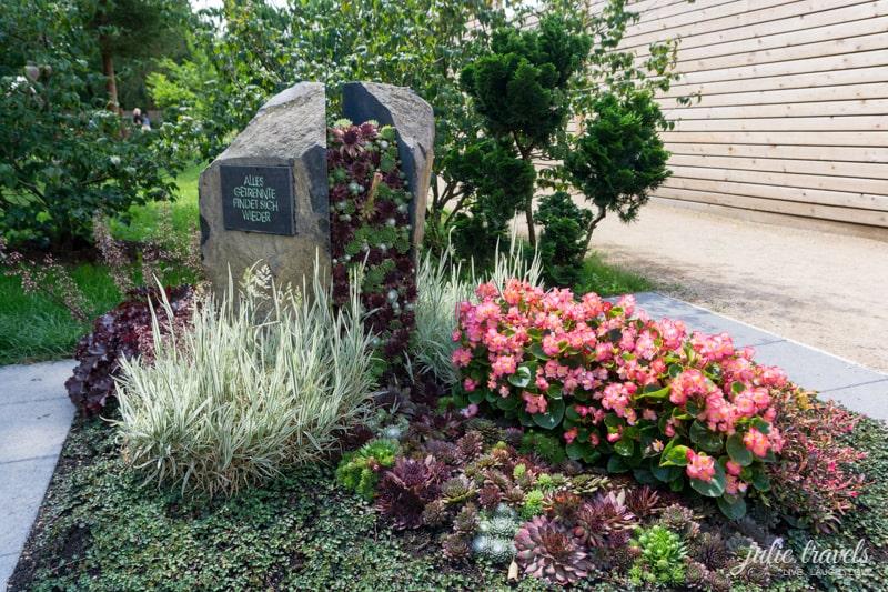 Ein zweigeteilter Grabstein mit Sukkulenten, die in der Mitte wachsen.