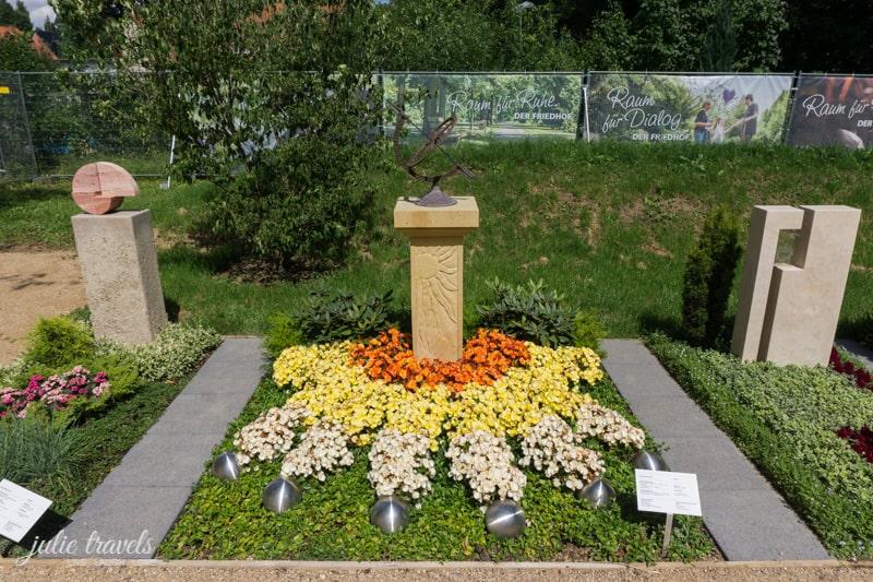 Eine Sonnenuhr als Grabstein mit passend gepflanzten Blumen.