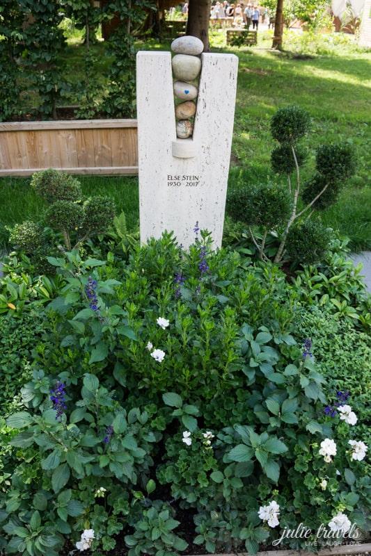 Ein heller Grabstein mit üppigen grünen Blumen und eingearbeiteten Steinen.