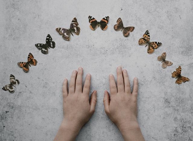 Zwei Kinderhände umgeben von Schmetterlingen